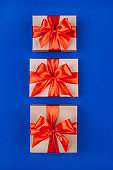Three cardboard gift boxes with bows on blue background.