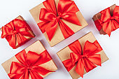 Cardboard gift boxes with red bows on white background.