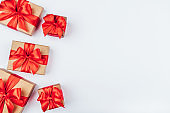 Frame of cardboard gift boxes with red bows.