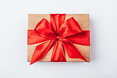Cardboard gift box with red bow on white background.