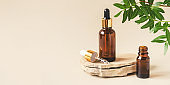 Two brown bottles of cosmetics on a natural beige background.