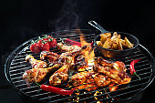 Grilled chicken legs or drumsticks on the hot flaming grill