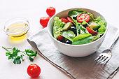 Fresh salad of avocado, cherry, arugula and olives made at home.