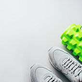 Grey sneakers and a massage roller on a gray background.