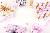 Several gift boxes with bows and confetti on a white background.