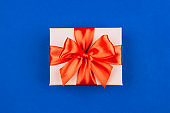 Cardboard gift box with red bow on blue background.
