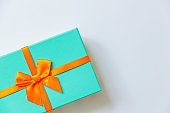 Christmas New Year birthday valentine celebration present romantic concept. Simply minimal design blue gift box with orange ribbon isolated on white background. Flat lay top view copy space