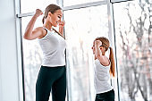 Mother and daughter showing strong hands in gym