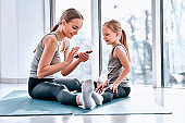 Mom and Daughter are doing yoga. Family in a gym. Little girl with mother in a white t-shirts and black leggings. Girls sitting on a green mat