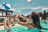 Young women plays in the pool with a beach ball
