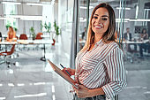 Close up view portrait of pretty cheerful business woman in an office environment holding laptop