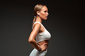 Side view of young sports fitness woman in sportswear working out isolated on grey background studio portrait.