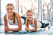 Mother and daughter working out together doing plank exercise
