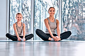 mother and daughter practicing yoga in butterfly pose at home