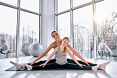 Mom and daughter do exercises on the mat. Mom with a child on a yoga mat smiling and sitting on the splits. Health family doing pilates.