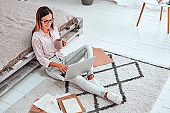 Young freelancer female working distantly from home by using portable computer connected to internet.