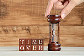 Wooden blocks with time over words and hourglass picked by human hand