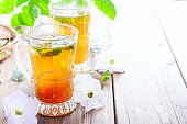 Black iced tea with lemon and mint in glass cups on a wooden table, horizontal, copy space