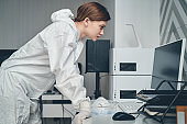 Beautiful young woman in protective suit using computer at work