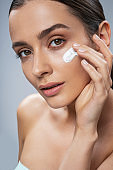 Amazing girl taking care of facial skin against grey background