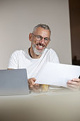Cheerful entrepreneur raising a piece of paper to his eyes