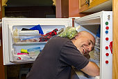 Man with head in freezer during heat wave