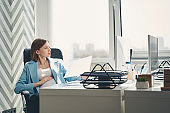 Charming pregnant woman working in modern office