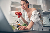 Caucasian positive lady cooking with vegetables in kitchen