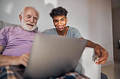 Young man and an elderly person spending time together
