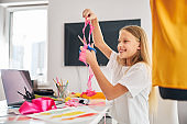 Cheerful seamstress scissoring off a strip of organza fabric