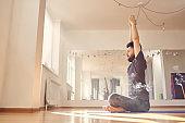 Bearded young man doing yoga exercise in studio