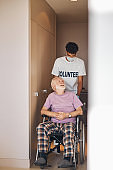 Volunteer in a face mask gazing at the disabled person