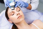 Female cosmetologist using an ultrasonic skin spatula