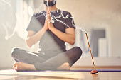 Young man practicing yoga in studio with incense stick