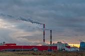 Smoking factory chimneys against the sunset. Environmental pollution