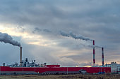 Smoky factory chimneys against a blue-gray sky. Environmental pollution