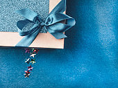 Christmas, weeding, Valentine day gift box or present with bow ribbon on trendy magic blue background. Copy space for greeting text.