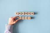 Hand holding wooden blocks with the word Trends 2021.