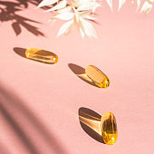 Liquid gelatin capsules with flower shadow on pink background