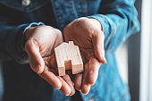 New home and real estate property concept, Woman holding wooden model house in hands.