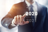 Businessman pointing year 2020 with sunlight effect. Business new year concept.