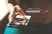 Love loading progress, Woman pushing heart icon on screen in mobile smartphone application. Online dating app, valentine's day concept.