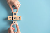 Health medical Insurance Concept, Two Hands arranging wood cube with medical symbol on pastel blue background.
