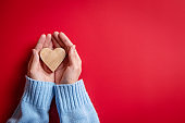 Female hands giving wood heart on red background, top view, copy space.