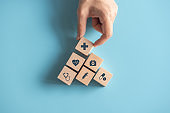 Health medical Insurance Concept, Hand arranging wood cube with medical symbol on pastel blue background, copy space.
