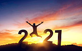 Silhouette young man jumping on the mountain and 2021 years while celebrating new year, happy victory and success concept.