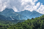 Green mountain slope with cable cars at cloudy summer day. Krasnaya Polyana, Sochi, Caucasus, Russia