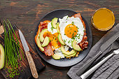 English breakfast - toast with bacon, avocado and egg on a plate. Healthy food. Top view