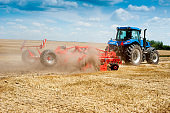 blue new tractor with red harrow in the field against a cloudy sky, agricultural machinery work raises dust