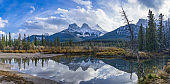 The Three Sisters trio peaks mountain reflect on water surface in autumn. Beautiful natural scenery landscape at Canmore, Canadian Rockies
